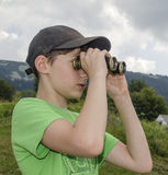 Boy is looking through binoculars Stock Photos