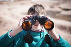 Boy looking with binoculars Stock Photos