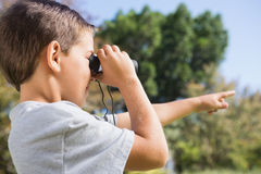 Boy looking through binoculars and pointing Stock Photo