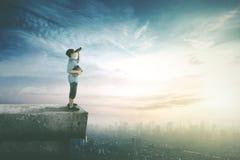 Boy looking with binoculars on rooftop Stock Image