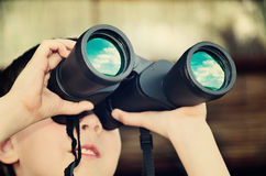 Boy looking through binoculars. toning effect with vanilla Royalty Free Stock Photo