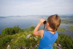 Boy looking through binoculars from the top of the mountain Stock Images