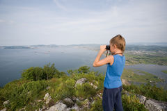 Boy looking through binoculars from the top of the mountain to t Stock Images