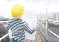 Boy looking blueprint in 3D scaffolding. Digital composite of Boy looking blueprint in 3D scaffolding Royalty Free Stock Photos