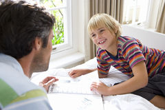 Boy (6-8) looking at book with father, smiling Royalty Free Stock Photo