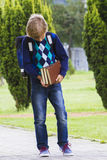 Boy looking at the books in his hands. Child go to school. Outdoor. Stock Photos