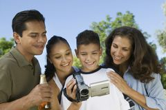 Boy (13-15) looking into camcorder with family outdoors. Royalty Free Stock Photography