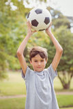 Boy looking at camera and holding a soccer ball in the park Royalty Free Stock Photo
