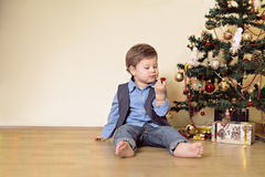 Boy looking at christmas ball in front of christmas tree. Boy looking at red Christmas ball in front of Christmas tree and presents Stock Photos