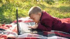 The boy is looking at the computer. Boy looking at computer lying on nature stock video