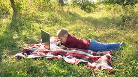 The boy is looking at the computer. Boy looking at computer lying on nature stock video footage