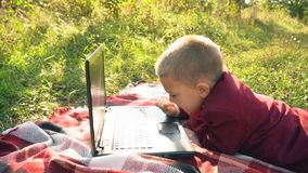 The boy is looking at the computer. Boy looking at computer lying on nature stock footage