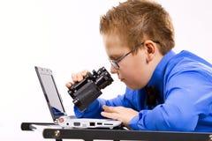 Boy looking at computer screen in binoculars Royalty Free Stock Photo