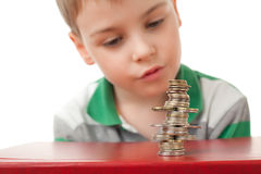 Boy looking at curve pile from coins Royalty Free Stock Image