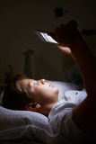 Boy Looking At Digital Tablet In Bed At Night Royalty Free Stock Image