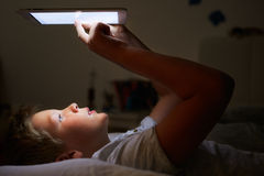 Boy Looking At Digital Tablet In Bed At Night Stock Image