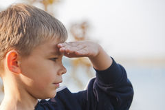 Boy looking at a distance. With eyes shaded royalty free stock photo