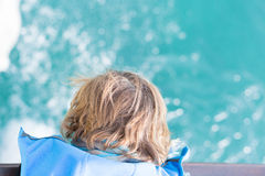 Boy looking down at water. From above. Royalty Free Stock Photography