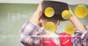Boy looking at emojis through VR glasses. Digital composite of Boy looking at emojis through VR glasses Stock Photography