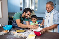 Boy looking at father breaking egg. While preparing food with grandfather in kitchen at home Royalty Free Stock Photos