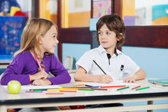 Boy Looking At Female Friend While Drawing In Stock Photo