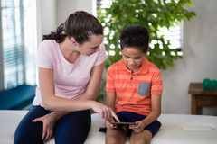 Boy looking while female therapist pointing at digital tablet. At hospital ward Stock Image