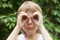 Boy Looking Through Fingers as Binoculars Royalty Free Stock Photography