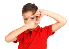 Boy looking through frame shape made by hands Stock Photos