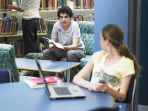 Boy Looking At Girl In Library Stock Images