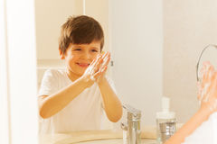 Boy looking in the glass while washing his hands royalty free stock photo