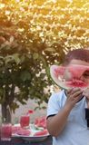 Boy looking through heart shape hole in a watermelon royalty free stock images