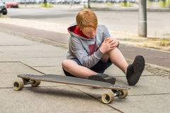 Boy Looking At His Injured Leg. Sitting Near Skateboard Royalty Free Stock Images
