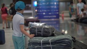 Boy looking for his suitcase on baggage conveyor belt at the airport. Child at baggage claim area of the airport. He looking over the suitcases on conveyor belt stock footage