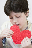 Boy looking his Valentine's card. Gray background stock image