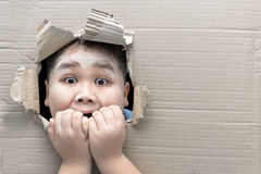 Boy looking through hole on cardboard with shocked face. Fat boy looking through hole on cardboard with funny shocked face expression, Halloween concept Royalty Free Stock Images