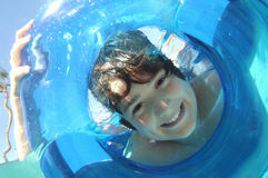 Boy Looking Through Inflatable Ring In Water Stock Photography