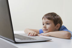 Boy looking at laptop computer. Education, learning, internet, homework and social media concept Royalty Free Stock Photo