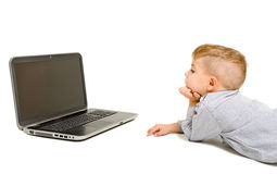 Boy looking at laptop lying on the floor Royalty Free Stock Photos