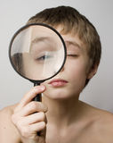Boy looking through the lens Stock Photo