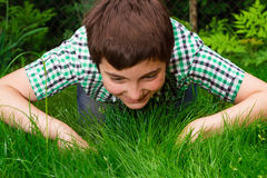 Boy looking for life in grass Royalty Free Stock Images