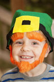 Leprechaun boy. Young boy smiling and wearing a leprechaun face with hat, eyebrows, and beard Royalty Free Stock Image