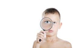 Boy looking through a magnifying Stock Photo