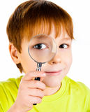 Boy looking through a magnifying glass Stock Images