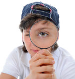 Boy looking through a magnifying glass Stock Photo