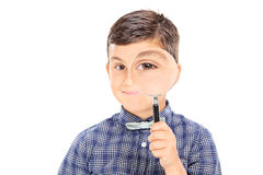 Boy looking through a magnifying glass Royalty Free Stock Photo