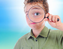 Boy looking through a magnifying glass Royalty Free Stock Image