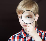 Boy looking through the magnifying glass Stock Photo