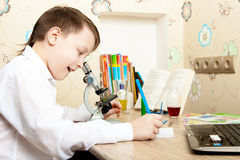 Boy looking through a microscope Stock Image