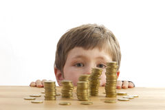 Boy looking at money. Boys looking at towers of money Royalty Free Stock Photo