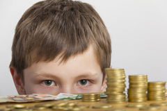 Boy looking at money. Boy looking at towers of money Royalty Free Stock Image